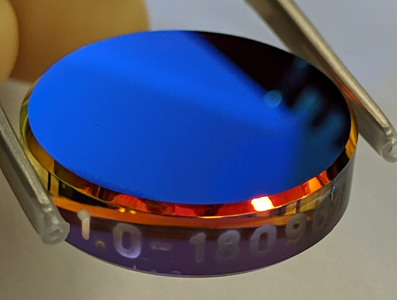 A colorful, reflective coating sample on 1-inch fused silica substrate