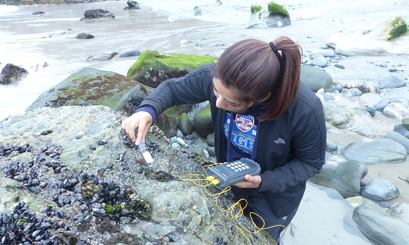 Student Alexis Barrera collects algae samples